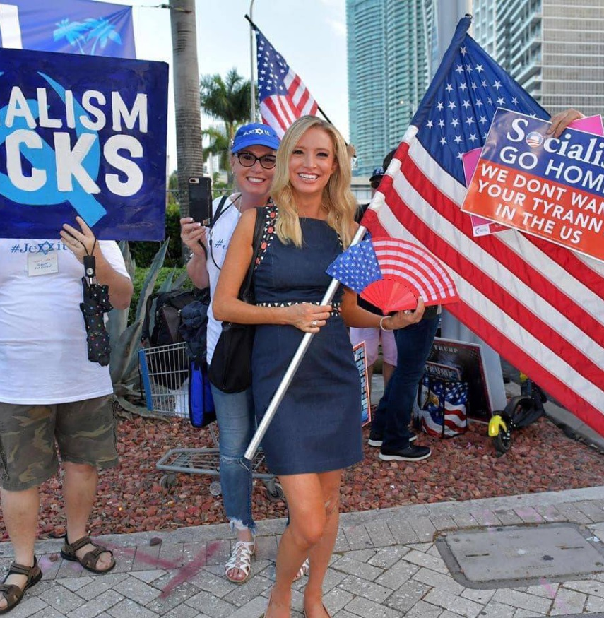 PHOTO Kayleigh McEnany Holding An American Flag That Says Socialists Go Home